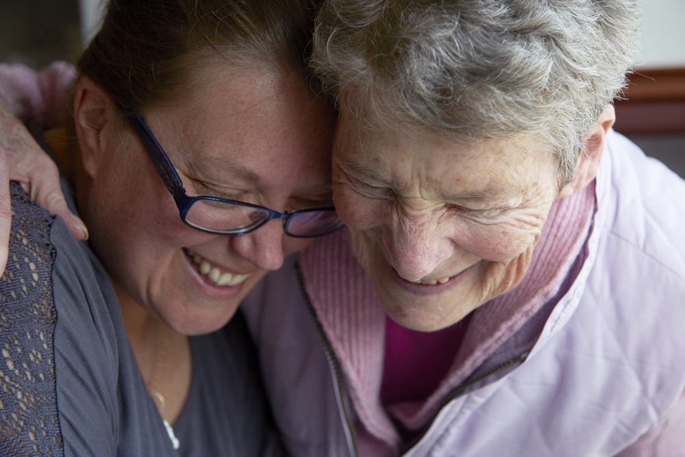 Elderly mother and daughter laughing together