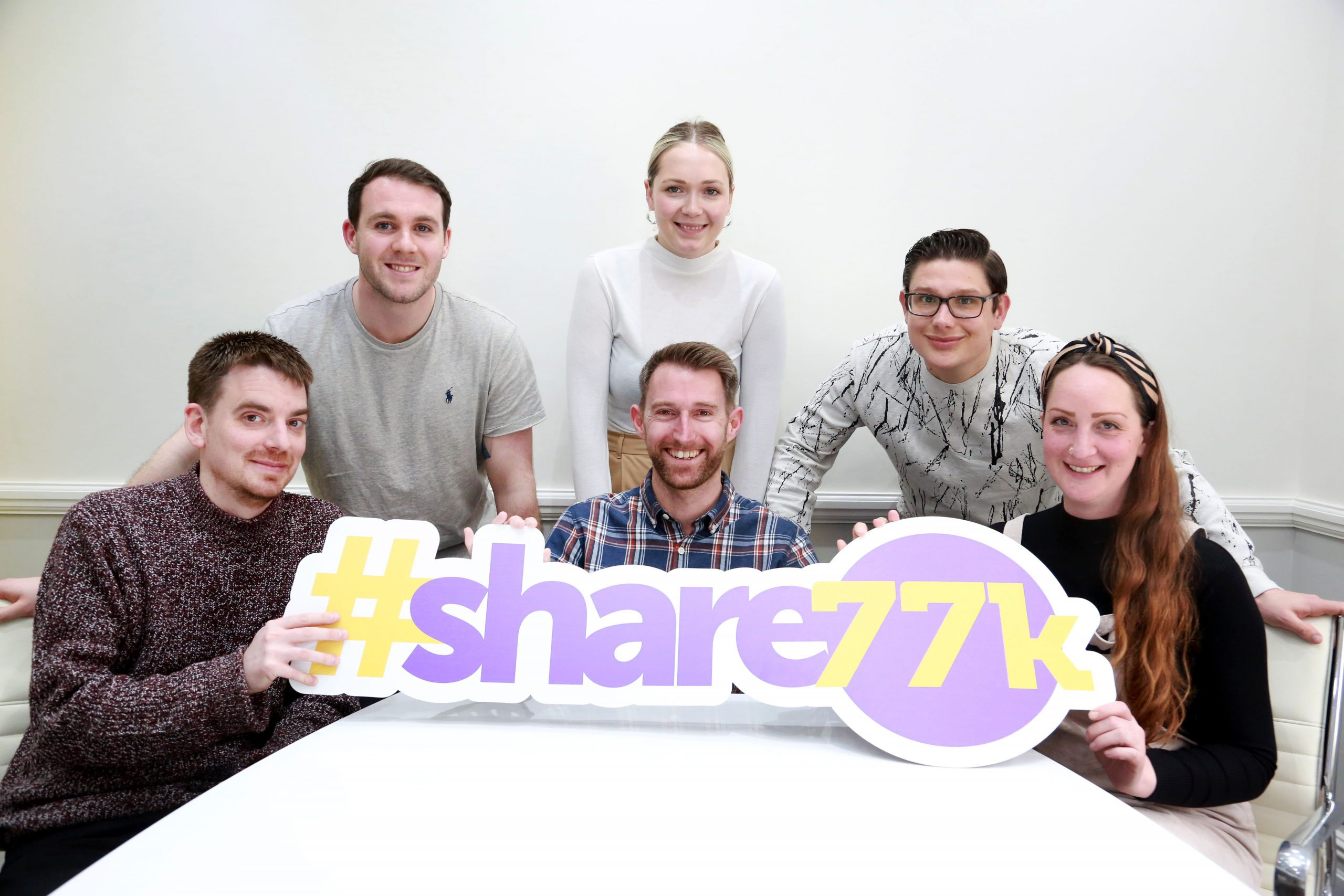 Photo of team holding #share77k sign
